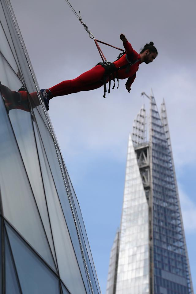 LONDON, ENGLAND - JULY 15:  A dancer walks down City Hall as part of the 'One Extraordinary Day' performances as The Shard is seen in the background on July 15, 2012 in London, England. The dancers are part of American choreographer Elizabeth Streb's 'extreem action' dance group which will perform around London for one day only and form part of the Cultural Olympiad.  (Photo by Dan Kitwood/Getty Images)