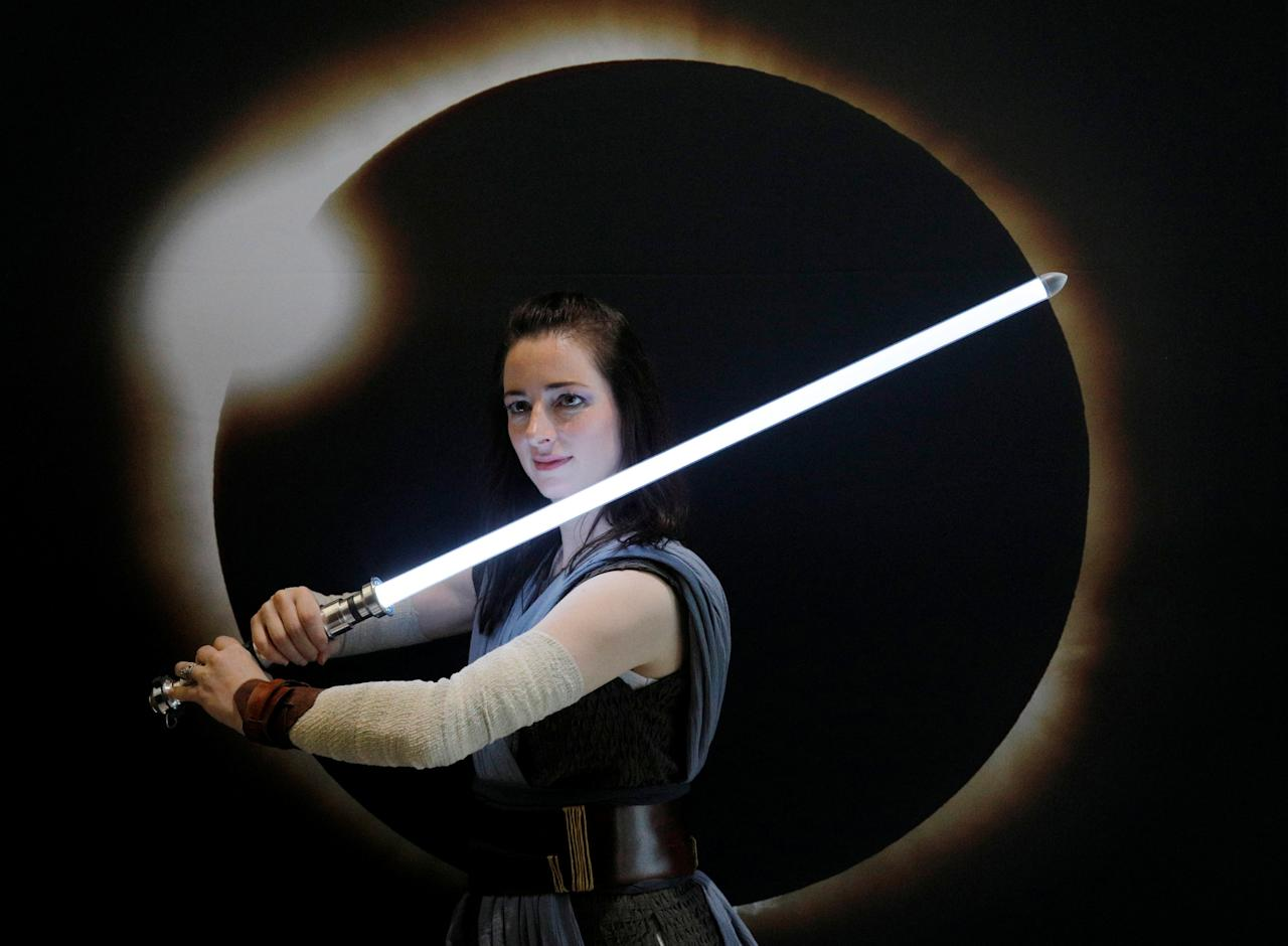 "A woman dressed as Rey from the upcoming Star Wars movie ""The Last Jedi"" poses for a photograph in front of an image of a solar eclipse at the Eclipse Comic-Con at Southern Illinois University in Carbondale, Illinois, U.S., August 20, 2017 one day before a total solar eclipse in the city. REUTERS/Brian Snyder"