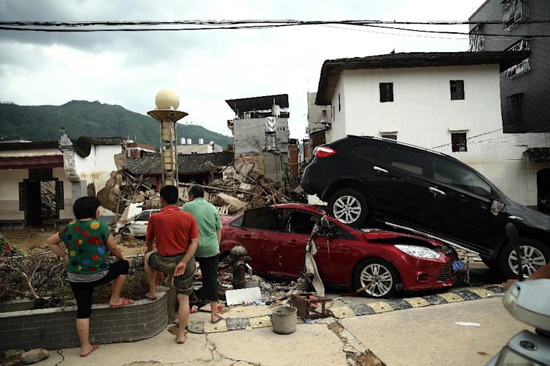 Residents looking at damaged cars and houses in the aftermath of a tropical storm in Bandong, China's Fujian province (AFP Photo/)