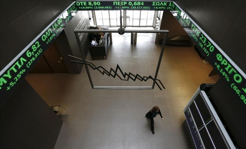 A woman walks inside the Athens stock exchange as a stock ticker shows stock options making major gains, inside the Athens stock exchange building February 24, 2015. REUTERS/Alkis Konstantinidis