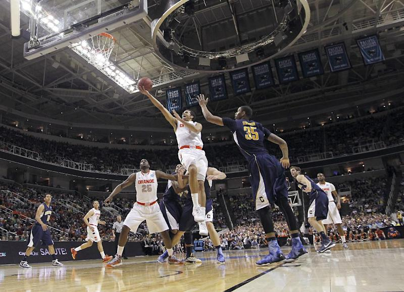 Syracuse guard Michael Carter-Williams (1) drives to the basket past California forward Richard Solomon (35) during the first half of a third-round game in the NCAA college basketball tournament Saturday, March 23, 2013, in San Jose, Calif.  (AP Photo/Tony Avelar)