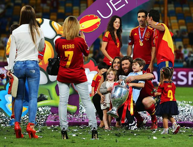 KIEV, UKRAINE - JULY 01: Xabi Alonso of Spain poses with his wife Nagore Aramburu, their son Jontxu Alonso (R) and the trophy following victory in the UEFA EURO 2012 final match between Spain and Italy at the Olympic Stadium on July 1, 2012 in Kiev, Ukraine. (Photo by Alex Grimm/Getty Images)