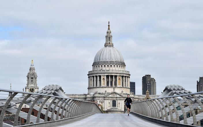 An all but deserted Millennium Bridge, linking the South Bank with St Paul's Cathedral, during the first Covid lockdown last March - Glyn Kirk/AFP
