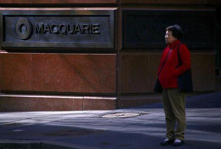 A pedestrian stands near the logo of Australia's biggest investment bank Macquarie Group Ltd which adorns a wall on the outside of their Sydney office headquarters in central Sydney, Australia, July 18, 2017. REUTERS/David Gray