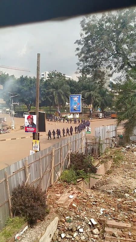 Security officers walk in line as smoke rises in the background in Kampala, Uganda