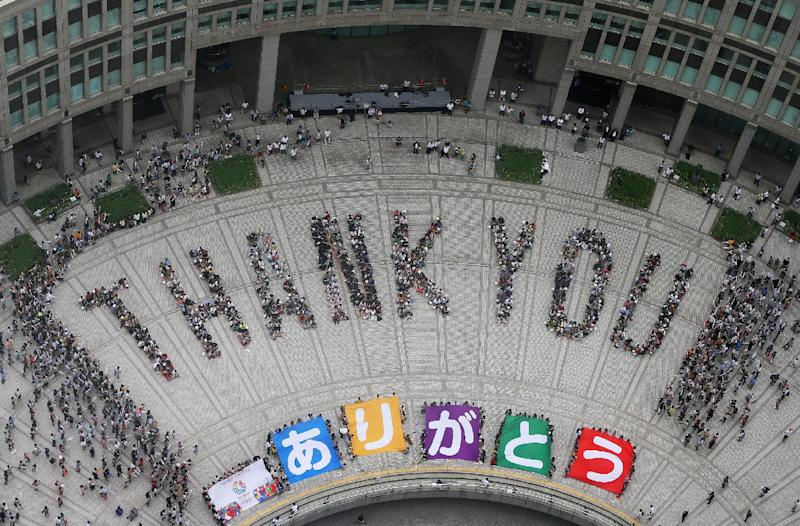 """People spell out the words """"THANK YOU"""" in Tokyo on September 8, 2013, after the Japanese city won the right to host the 2020 Olympics (AFP Photo/)"""