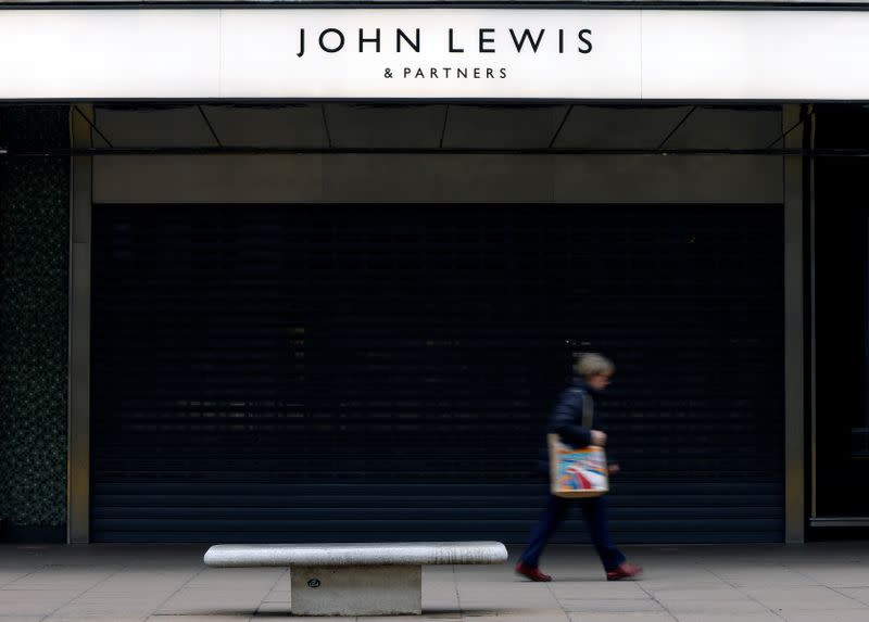 A woman walks past a temporarily closed John Lewis department store on Oxford Street in London
