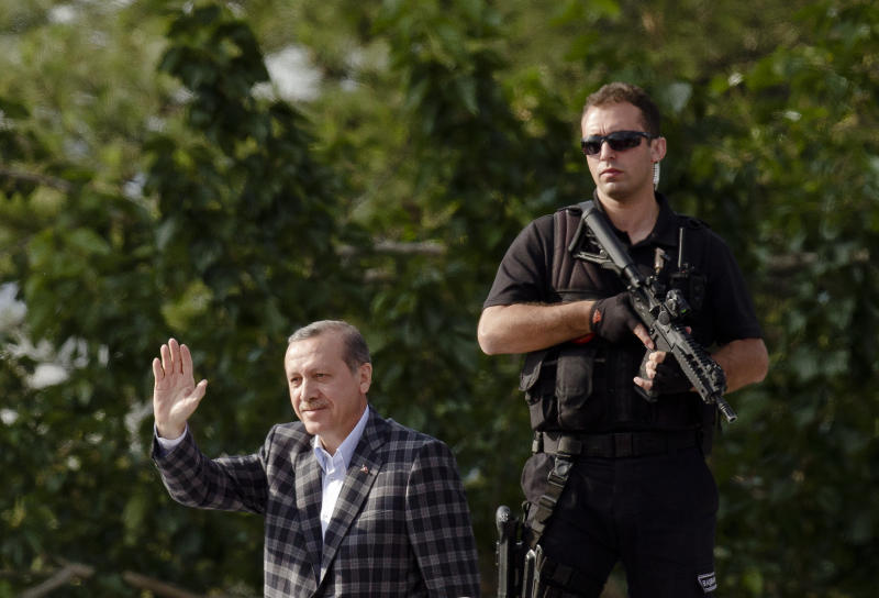 "Turkish Prime Minister Recep Tayyip Erdogan waves to supporters upon arriving in Ankara, Turkey, Sunday, June 9, 2013. In a series of increasingly belligerent speeches to cheering supporters Sunday, Turkey's prime minister launched a verbal attack on the tens of thousands of anti-government protesters who flooded the streets for a 10th day, accusing them of creating an environment of terror. Recep Tayyip Erdogan made the most inflammatory of his speeches as he arrived in the capital, Ankara. Erdogan belittled his opponents, again calling them ""capulcu,"" the Turkish word for looters or vandals. He made his speech in Ankara atop an open-top bus, which then drove into the city in a motorcade. (AP Photo/Vadim Ghirda)"
