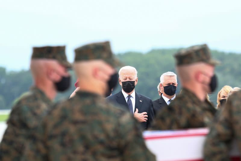 U.S. President Joe Biden salutes during the dignified transfer of the remains of U.S. Military service members who were killed by a suicide bombing at the Hamid Karzai International Airport