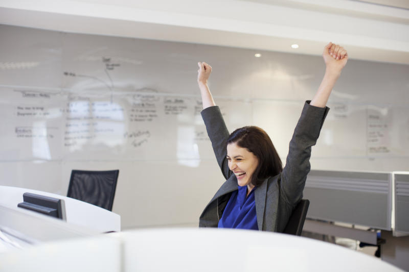 A woman throws her arms in the air in joy.