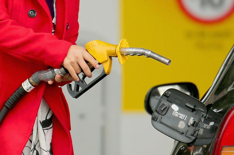 A woman uses a fuel dispenser to fill her car up with petrol at a petrol station on July 23, 2013 in Melbourne, Australia.