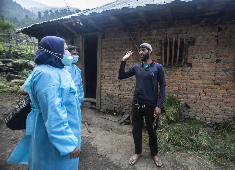 Health workers talk to Bilal Chauhan, a local villager, to persuade him to take the COVID-19 vaccine in Minnar village, north of Srinagar, Indian controlled Kashmir, Thursday, June 10, 2021. Chauhan and many other villagers refused to take vaccine saying the were from the mountains and too hardy to be affected by the virus. (AP Photo/Mukhtar Khan)