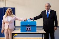 FILE PHOTO: Israeli Prime Minister Benjamin Netanyahu and his wife Sara casts their votes during Israel's parliamentary election at a polling station in Jerusalem