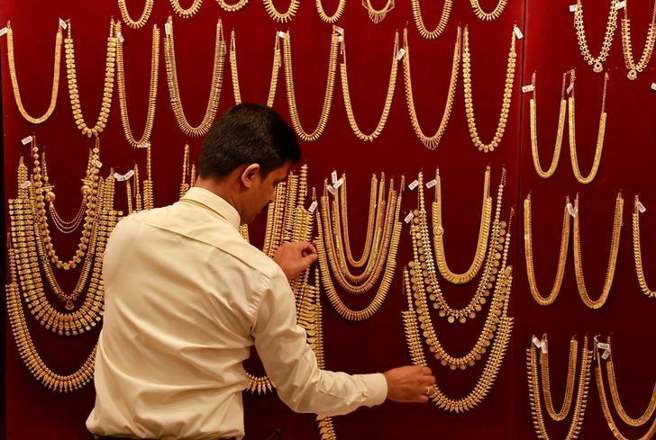 Salesman arranges gold ornaments on display board inside a jewellery showroom during Akshaya Tritiya, a major gold buying festival, in Kochi