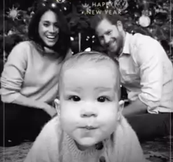 Meghan Markle and Prince Harry watch Archie in the foreground if the photo staring into the camera