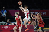 Japan's Nanako Todo, center, catches a pass over Belgium's Kim Mestdagh, left, and Julie Allemand, right, during a women's basketball quarterfinal round game at the 2020 Summer Olympics, Wednesday, Aug. 4, 2021, in Saitama, Japan. (AP Photo/Charlie Neibergall)