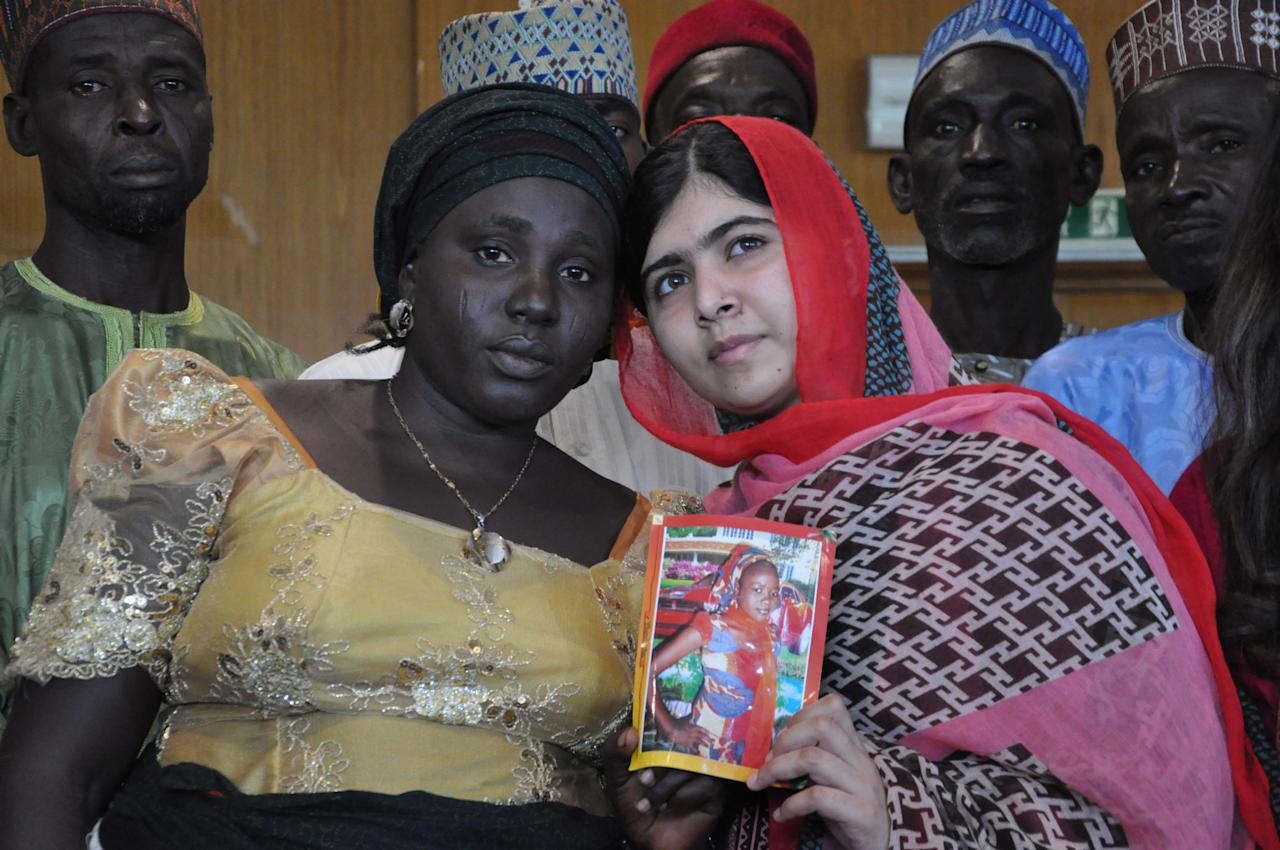 Pakistani activist Malala Yousafzai who survived being shot by the Taliban because she advocated education for girls, holds a picture of kidnapped schoolgirl Sarah Samuel with her mother Rebecca Samuel, during a visit to Abuja, Nigeria, Sunday July 13, 2014. Malala Yousafzai traveled to Abuja in Nigeria to meet the relatives of schoolgirls who were kidnapped by Boko Haram three months ago. (AP Photo/Olamikan Gbemiga)