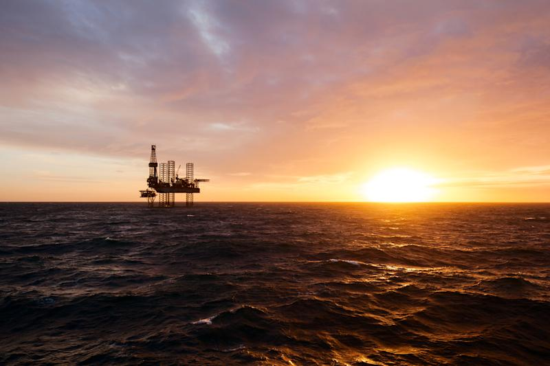 The silhouette of an offshore drilling rig at sunset.