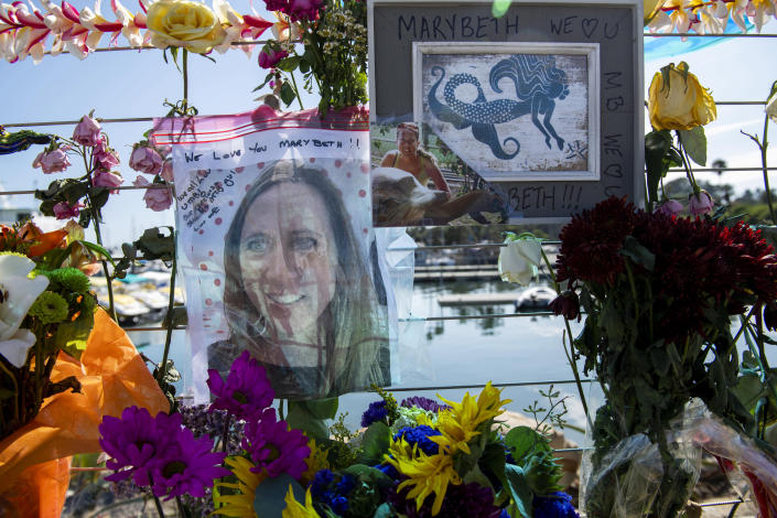 Photographs of loved ones lost in the fire on the scuba boat Conception are placed at a memorial on the Santa Barbara Harbor on Wednesday, Sept. 4, 2019, in Santa Barbara, Calif. A fire raged through the boat carrying recreational scuba divers anchored near an island off the Southern California Coast on Monday, leaving multiple people dead. (AP Photo/Christian Monterrosa )
