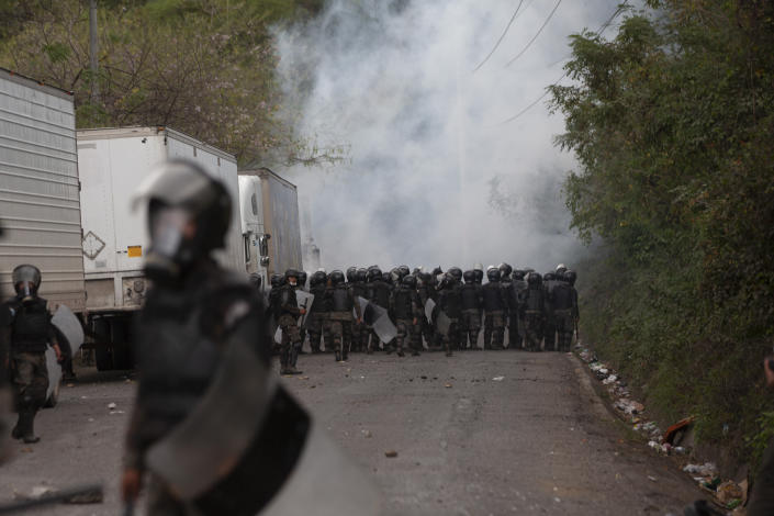 A cloud of teargas rises as Guatemalan soldiers and police clash with migrants at a roadblock on the highway in Vado Hondo, Guatemala, Monday, Jan. 18, 2021. The roadblock was strategically placed at a chokepoint on the two-lane highway flanked by a tall mountainside and a wall leaving the migrants with few options. (AP Photo/Sandra Sebastian)