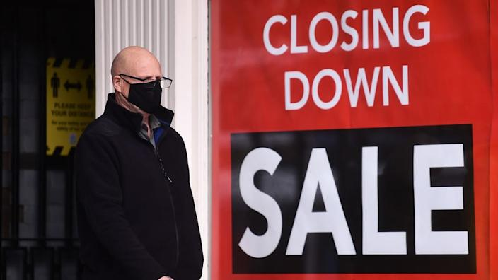 Masked man walking in front of shop closure sign