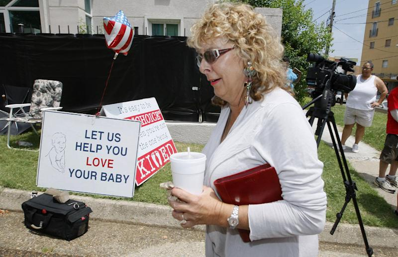 FILE- In this Monday, July 2, 2012, file photo, Jackson Women's Health Organization owner Diane Derzis, walks past abortion opponents protesting outside Mississippi's only abortion clinic in Jackson, Miss. Restricting abortion has long been a conservative goal in Mississippi, and now, a Republican-appointed federal judge is considering the constitutionality of the state's stringent new abortion law. (AP Photo/Rogelio V. Solis, File)