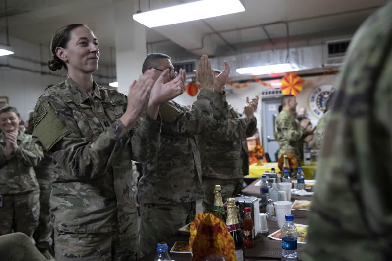 Members of the military applaud as President Donald Trump speaks at a dinning facility during a surprise Thanksgiving Day visit, Thursday, Nov. 28, 2019, at Bagram Air Field, Afghanistan. (AP Photo/Alex Brandon)