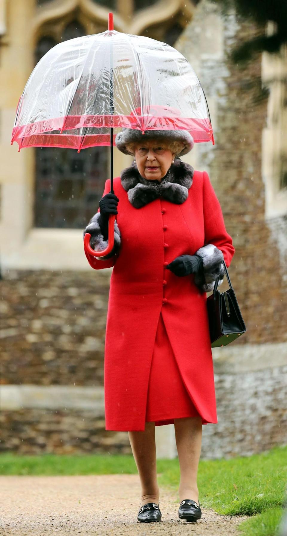 <p>The Queen even matched her umbrella to her vibrant red coat for the Christmas Day church service.<br><i>[Photo: PA]</i> </p>