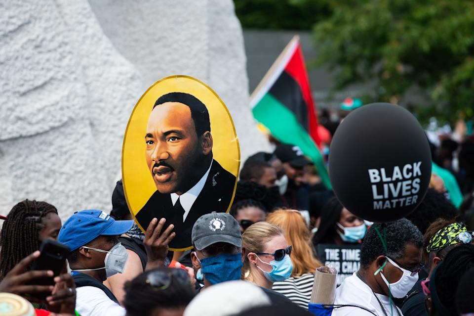 A protester carries an image of Martin Luther King Jr. during a protest against racism and police brutality on Aug. 28, 2020, in Washington, D.C. (Photo: ROBERTO SCHMIDT/AFP via Getty Images)