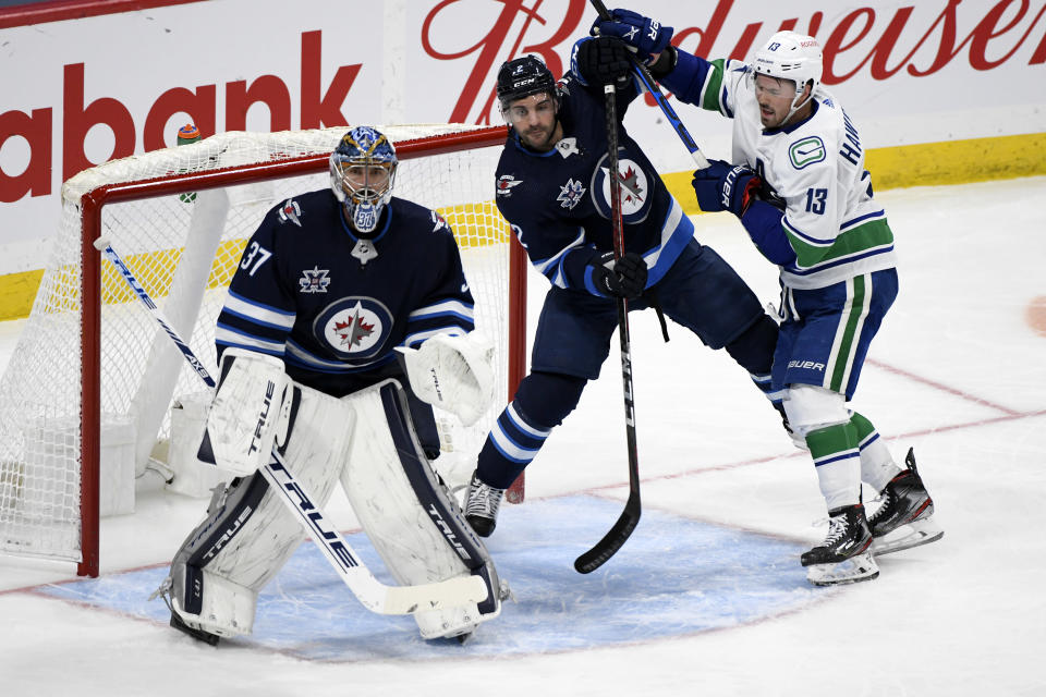 Winnipeg Jets' Dylan DeMelo (2) and Vancouver Canucks' Jayce Hawryluk (13) work for position beside Jets goaltender Connor Hellebuyck (37) during the second period of an NHL hockey game Tuesday, May 11, 2021, in Winnipeg, Manitoba. (Fred Greenslade/The Canadian Press via AP)