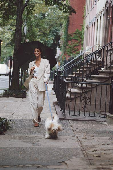 <p>An all-white ensemble for the win. With an oversized jacket and pants, a high-waisted belt, and an umbrella without rain, walking the dog has never looked better.</p>