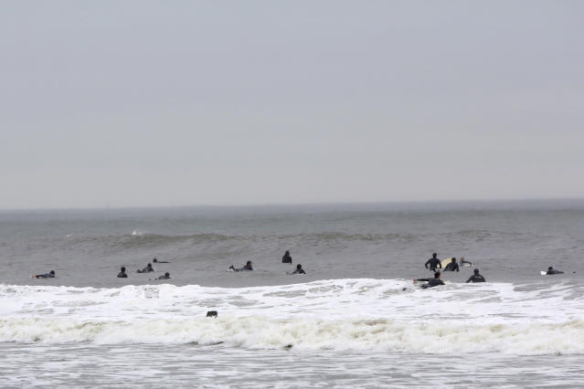 FILE - In this file photo of May 24, 2013 photo, surfers wait to catch waves at Rockaway Beach in the Queens borough of New York. Superstorm Sandy hit the Rockaways hard last fall, flooding homes and stores, eroding the beach in some spots and destroying the boardwalk, but subway service has been restored, small businesses are reopening, and the beaches are attracting plenty of visitors. (AP Photo/Mary Altaffer, File)