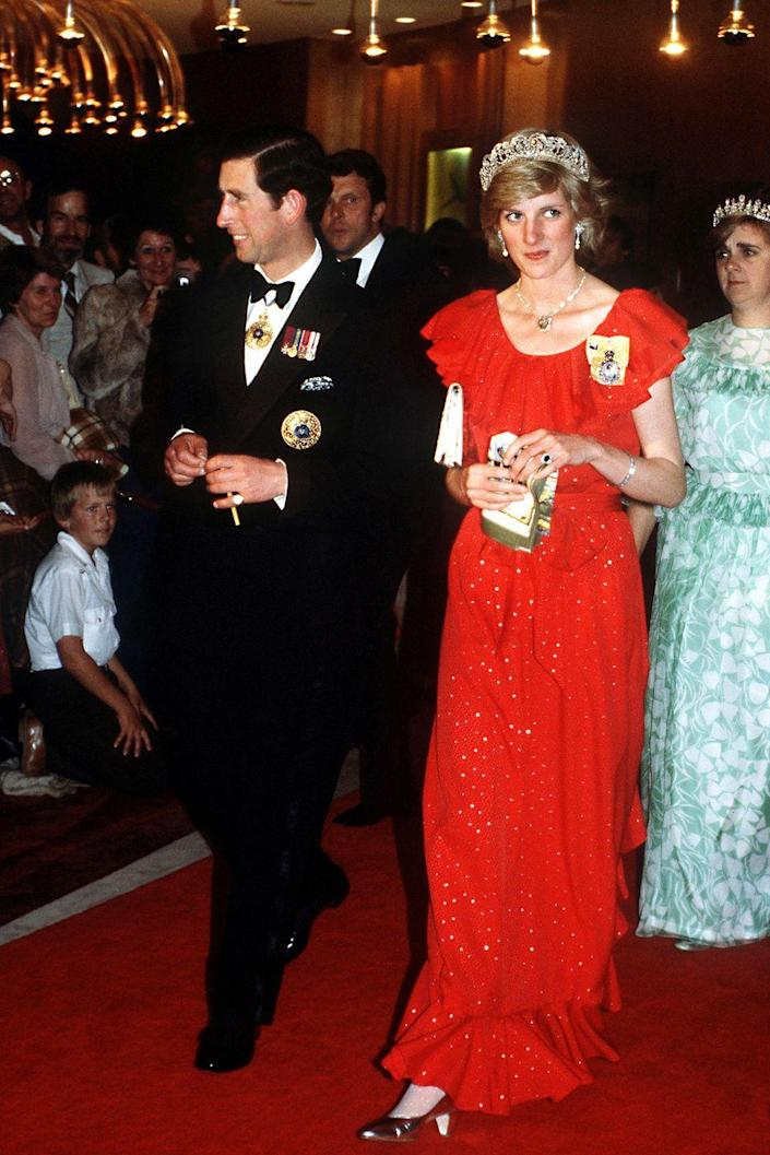 <p>Charles and Diana attend a reception in Hobart, Tasmania. She wears a red Bruce Oldfield dress with the Spencer family tiara. </p>