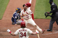 St. Louis Cardinals' Austin Dean (0) celebrates after scoring past Milwaukee Brewers catcher Omar Narvaez as Cardinals' John Nogowski (34) cheers during the sixth inning of a baseball game Saturday, April 10, 2021, in St. Louis. (AP Photo/Jeff Roberson)