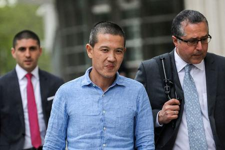 FILE PHOTO: Ex-Goldman Sachs banker Roger Ng (center) and his lawyer leave the federal court in New York