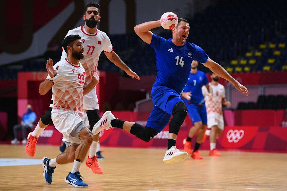 <p>France's centre back Kentin Mahe (R) jumps to shoot past Bahrain's centre back Husain Al Sayyad (L) and Bahrain's left back Ali Merza Salman Abdulla Ali during the men's quarterfinal handball match between France and Bahrain of the Tokyo 2020 Olympic Games at the Yoyogi National Stadium in Tokyo on August 3, 2021. (Photo by Franck FIFE / AFP)</p>