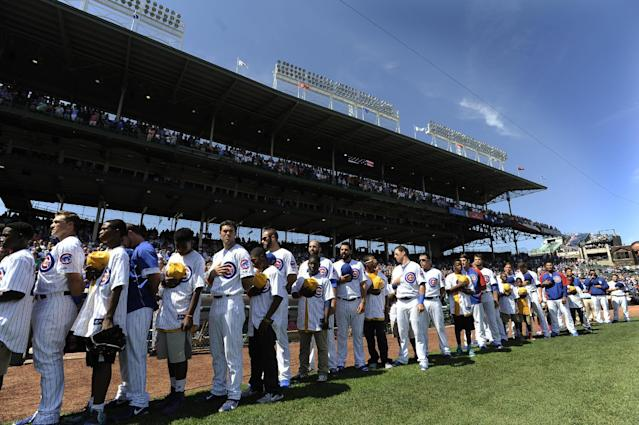 The Jackie Robinson West little league team stands with the Chicago Cubs team during the singing of the national anthem before a baseball game between the Chicago Cubs and Milwaukee Brewers at Wrigley Field in Chicago, Monday, Sept. 1, 2014. (AP Photo/Paul Beaty)