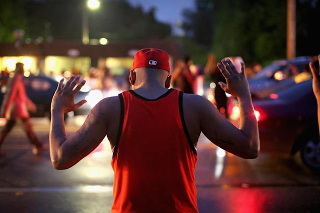A black man stands during a demonstration with his hands raised. (Scott Olson via Getty Images)