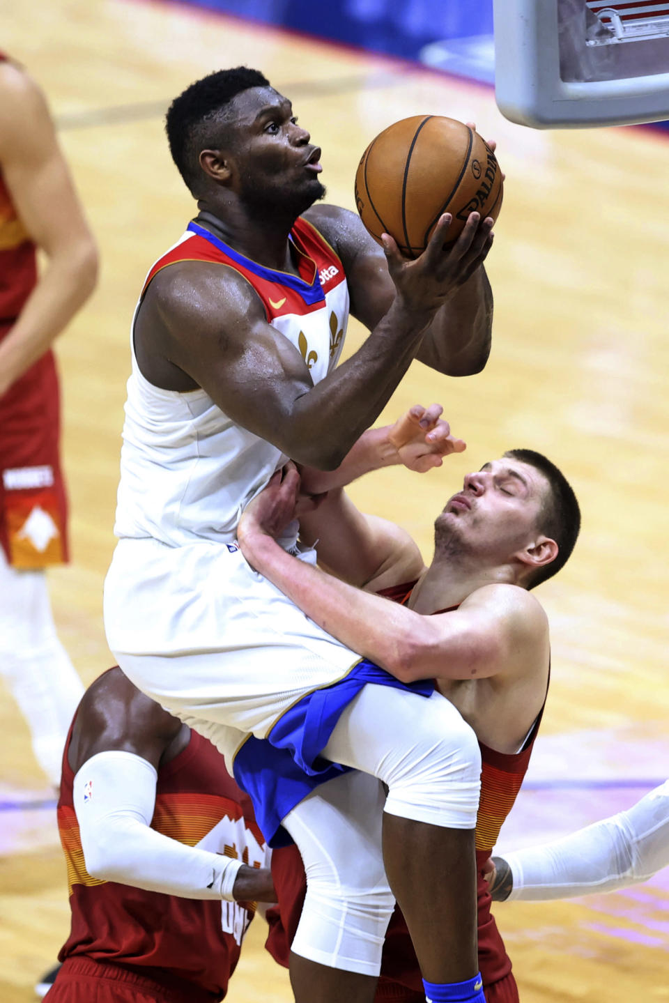 New Orleans Pelicans forward Zion Williamson (1) drives to the basket as Denver Nuggets center Nikola Jokic defends during the second half of an NBA basketball game in New Orleans, Friday, March 26, 2021. (AP Photo/Rusty Costanza)