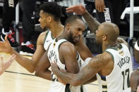 Milwaukee Bucks' Giannis Antetokounmpo, from left, celebrates with Khris Middleton and P.J. Tucker during the second half of Game 5 of basketball's NBA Finals against the Phoenix Suns, Saturday, July 17, 2021, in Phoenix. (AP Photo/Matt York)