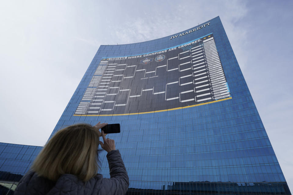 Lisa Moeller takes a photo of the NCAA bracket for the NCAA college basketball tournament on the side of the JW Marriott in downtown Indianapolis. Wednesday, March 17, 2021. (AP Photo/Darron Cummings)