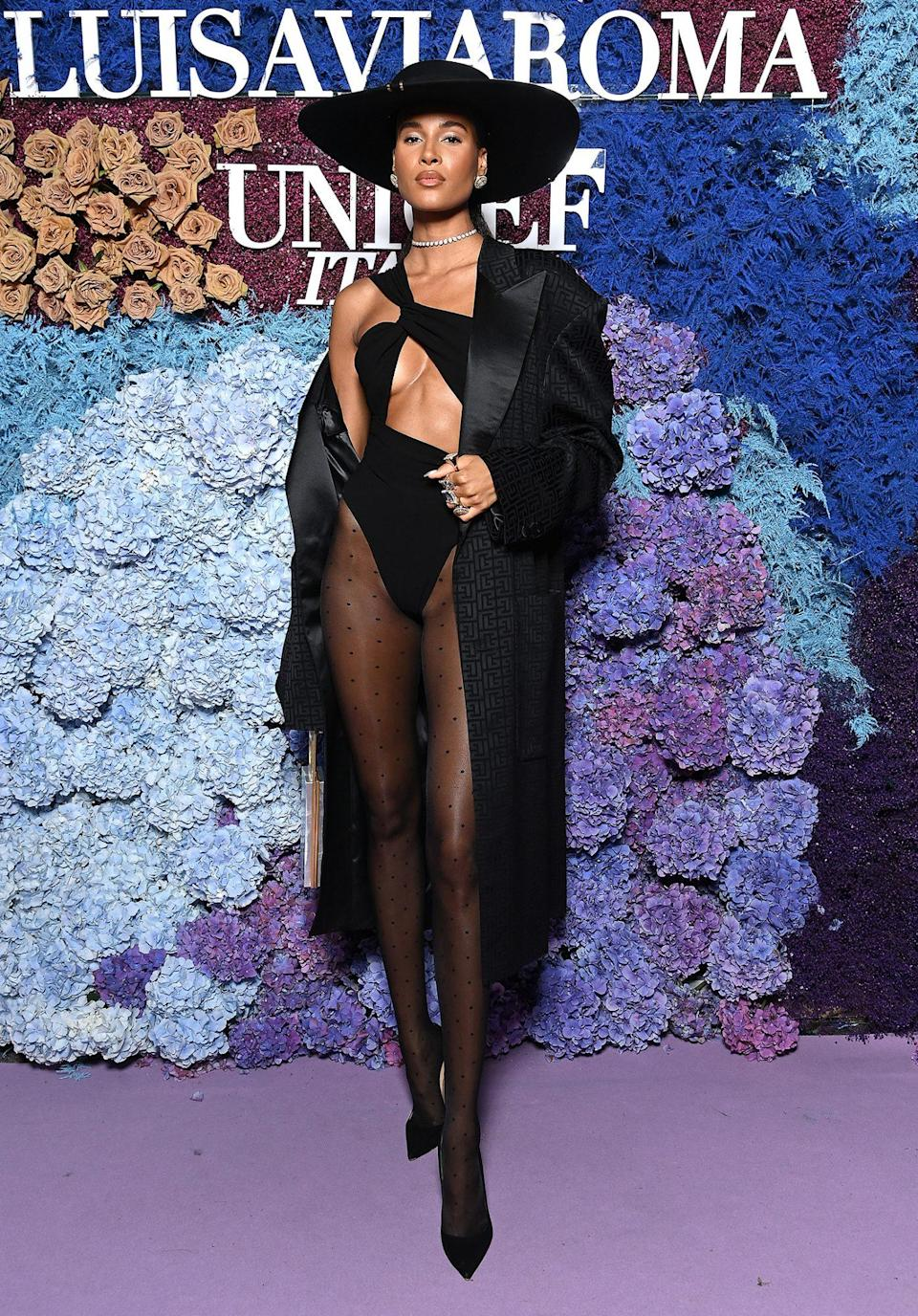 <p>teams a black cutout bodysuit with sheer tights, black tuxedo jacket, wide-brim hat and Christian Louboutin heels.</p>