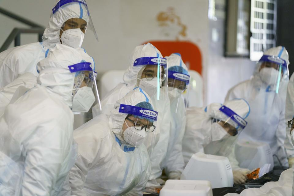 Medical worker wearing personal protective equipment (PPE) listen to briefing at a COVID-19 testing center in Shah Alam city, Selangor states, Malaysia, Wednesday, Feb. 17, 2021. The second movement control order (MCO) currently enforced across the country, has been extended to March. 4 in some of the states, to try to halt the spread of the coronavirus. (AP Photo/Vincent Thian)