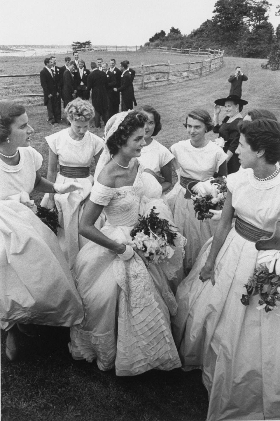 <p>Jackie wears her ivory silk wedding gown with a portrait neckline and a ruffled bouffant skirt, which was designed by custom New York City dressmaker Ann Lowe. </p>