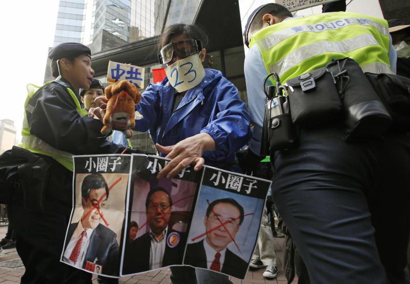 Protesters display a poster of three candidates, from right, former convener of Hong Kong's Executive Council, Leung Chun-ying,  Democratic Party chairman Albert Ho and Former Hong Kong Chief Secretary Henry Tang during a demonstration against Beijing's involvement in Hong Kong's chief executive election outside a polling station in Hong Kong, Sunday, March 25, 2012. Hong Kong's elite voted Sunday to choose the city's next leader following a tumultuous, bitter race that highlighted public discontent in the southern Chinese financial hub. (AP Photo/Vincent Yu)