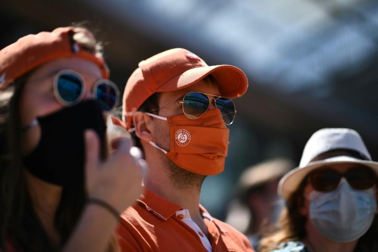 Cover up: Spectators wearing protective face masks at Roland Garros on Sunday