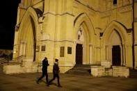 People walk outside the Archcathedral Basilica of St. Stanislaus Kostka in Lodz