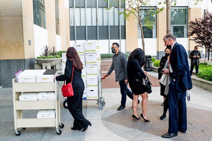 Members of Apple's legal team roll exhibit boxes into the Ronald V. Dellums building in Oakland, Calif., as the company faces off in federal court against Epic Games on Monday, May 3, 2021.