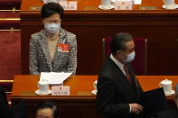 Hong Kong Chief Executive Carrie Lam sits as Chinese Foreign Minister Wang Yi, right, arrives before the opening session of China's National People's Congress (NPC) at the Great Hall of the People in Beijing, Friday, March 5, 2021. (AP Photo/Andy Wong)