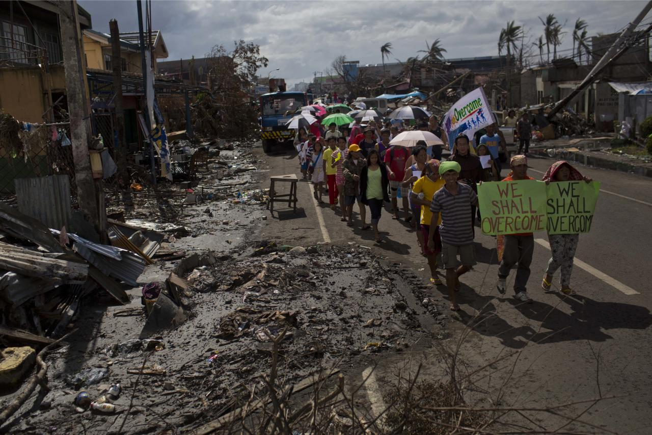 People march in the rain Tacloban, Philippines during a procession to call for courage and resilience among their Typhoon Haiyan survivors on Tuesday Nov. 19, 2013. In the wake of every major global catastrophe, the world's media dutifully broadcasts the traditional narrative of grief and despair. Stories of loss and desperation were ubiquitous in Haiyan as well, and rightly so: more than 4,000 people were killed in the storm's first few hours, and blackened bodies with skin peeling are still trapped under the rubble today. But as the crisis eases and aid begins to flow, there is another side to the story that rarely gets beamed out _ people smiling (if only briefly), people joking (if only in passing). (AP Photo/David Guttenfelder)